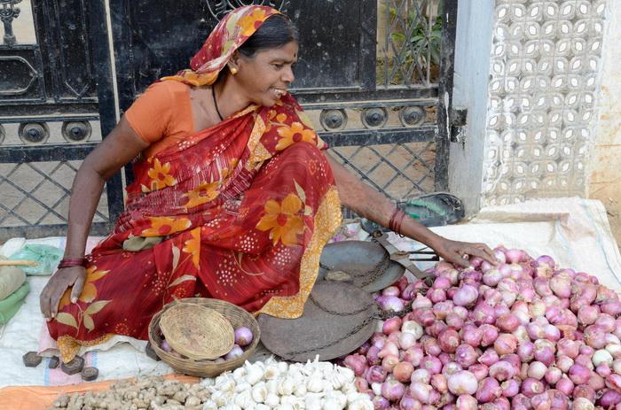Женщина в индийской одежде торгует чесноком