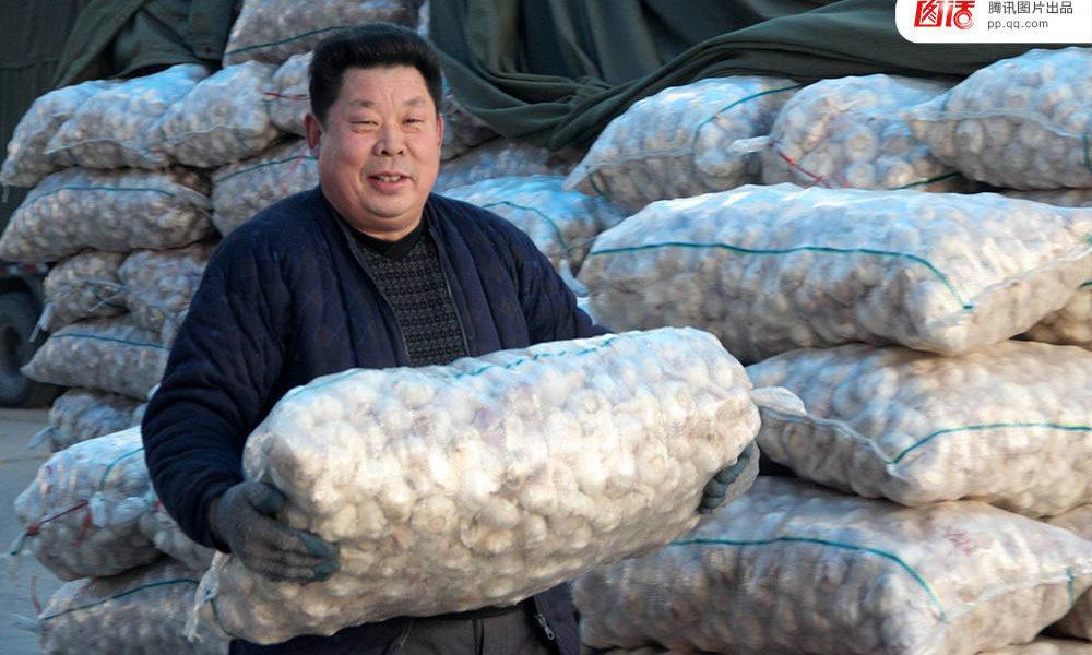 торговец на рынке чеснока в китае с мешком чеснока в руках